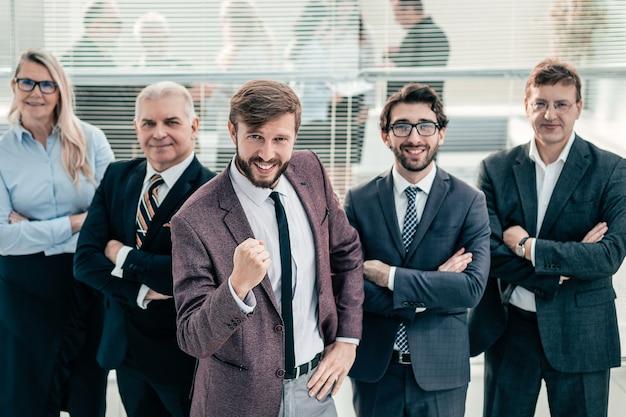 Szczęśliwy biznesmen i grupa czołowych ekspertów stojących razem