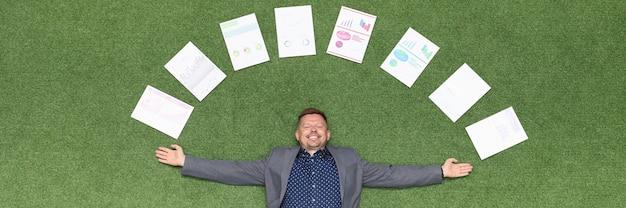 Szczęśliwy biznesmen leży na zielonym trawniku w dokumentach z wykresami biznesowymi