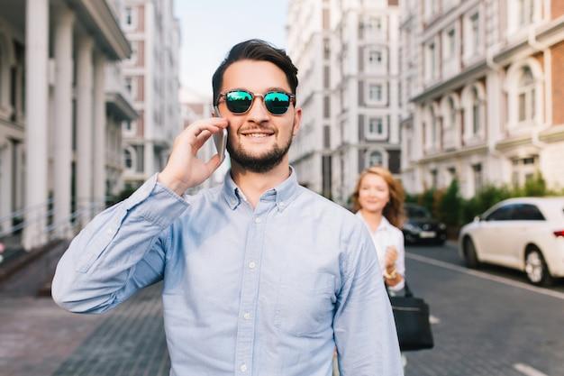 Szczęśliwy biznesmen mówi na telefon na ulicy w okularach przeciwsłonecznych. ładna blondynka łapie go od tyłu