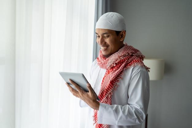 Szczęśliwy biznesmen muzułmański uśmiecha się podczas korzystania z komputera typu tablet w pobliżu okna