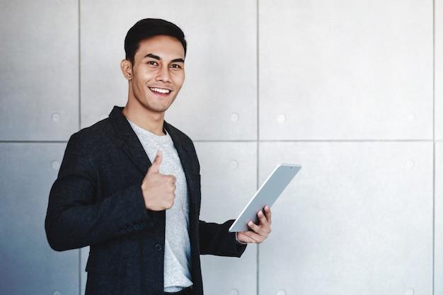 Szczęśliwy biznesmen ono uśmiecha się aprobaty i pokazuje podczas gdy używać cyfrowej pastylkę
