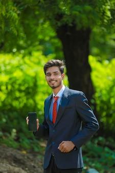 Szczęśliwy biznesmen palcem wskazującym na pustym ekranie smartfona