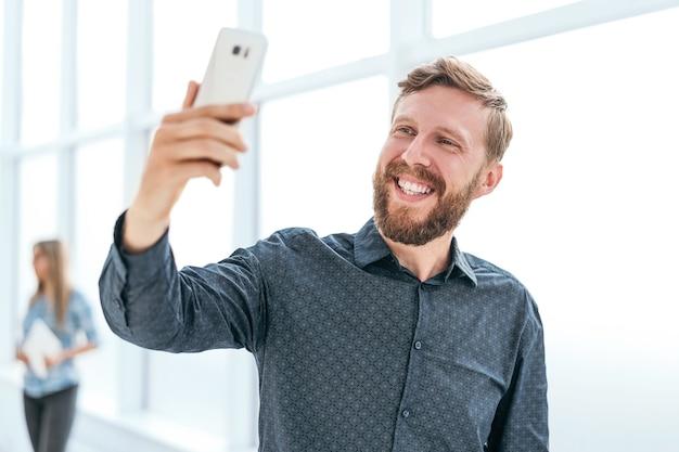 Szczęśliwy biznesmen patrząc na ekran swojego smartfona