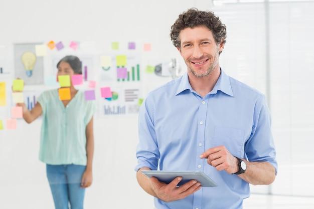Szczęśliwy biznesmen patrzeje kamerę z kolegą behind