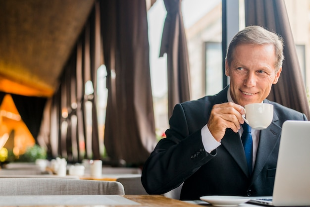 Szczęśliwy biznesmen pije kawę z laptopem na biurku