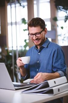 Szczęśliwy biznesmen pije kawowy patrzejący telefon komórkowego w kreatywnie biurze