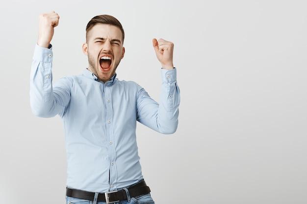 Szczęśliwy biznesmen pompka pięścią, krzyczący tak, wygrywający nagrodę, triumfujący nad zwycięstwem