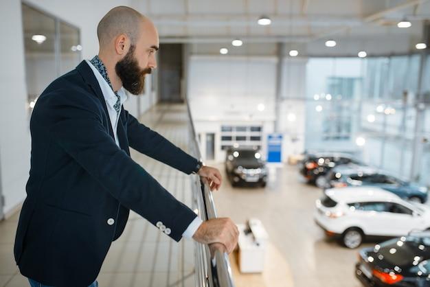 Szczęśliwy biznesmen pozuje w salonie samochodowym. klient w nowym salonie samochodowym, mężczyzna kupujący samochód, firma dealera samochodowego dealer