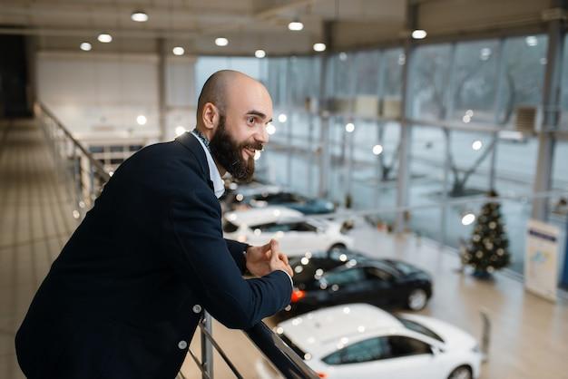 Szczęśliwy biznesmen pozuje w salonie samochodowym