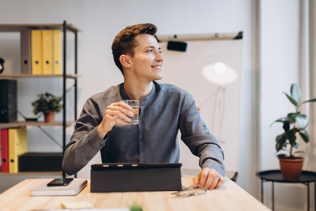 Szczęśliwy biznesmen pracuje przy jego biurem z laptopem. młody uśmiechnięty mężczyzna obsiadanie przy jego miejscem pracy z notebookiem i trzymający szklankę wody w ręce