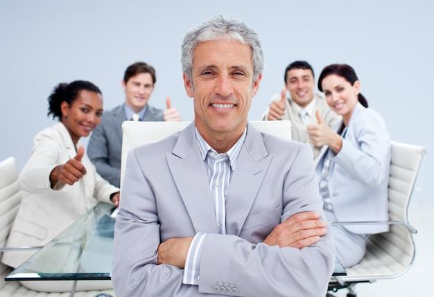 Szczęśliwy biznesmen prowadzi jego szczęśliwej drużyny z aprobatami