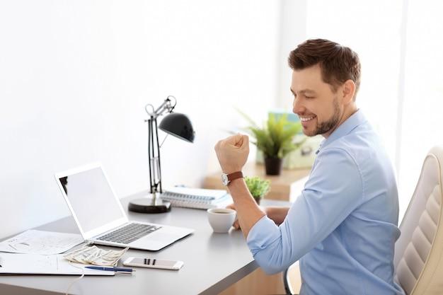 Szczęśliwy biznesmen przy stole w biurze