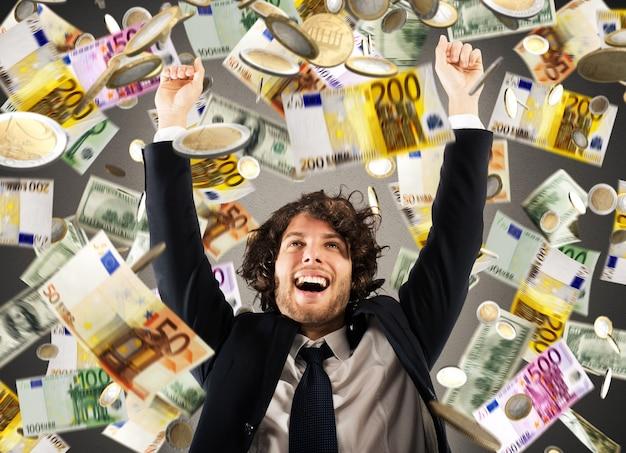 Szczęśliwy biznesmen raduje się pod deszczem monet i banknotów