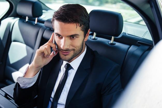 Szczęśliwy biznesmen rozmawia przez telefon w samochodzie