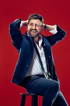Szczęśliwy biznesmen siedzi i uśmiecha się na białym tle na czerwonym tle studio.