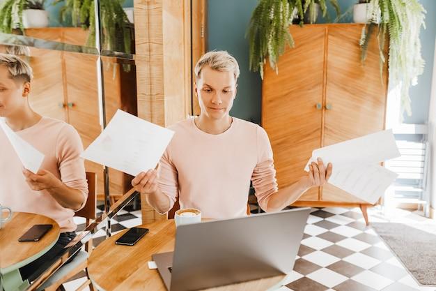 Szczęśliwy biznesmen siedzi w kawiarni z laptopem i dokumentami. biznesmen siedzi w kawiarni, pracuje i sprawdza pocztę na komputerze