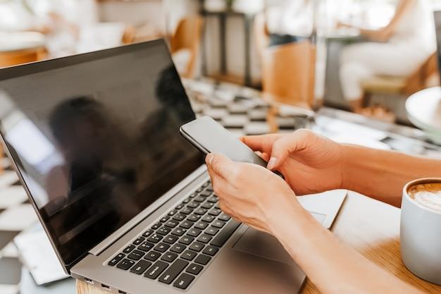 Szczęśliwy biznesmen siedzi w kawiarni z laptopem i smartfonem. biznesmen sms-y na smartfonie siedząc w kawiarni, pracując i sprawdzając pocztę na komputerze