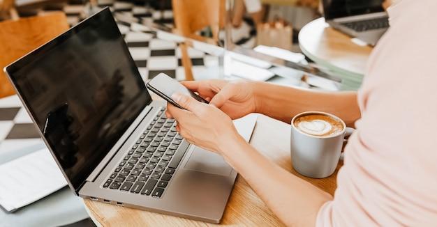 Szczęśliwy biznesmen siedzi w kawiarni z laptopem i smartfonem. biznesmen wysyłanie sms-ów na inteligentny telefon siedząc w kawiarni, pracując i sprawdzając pocztę na komputerze
