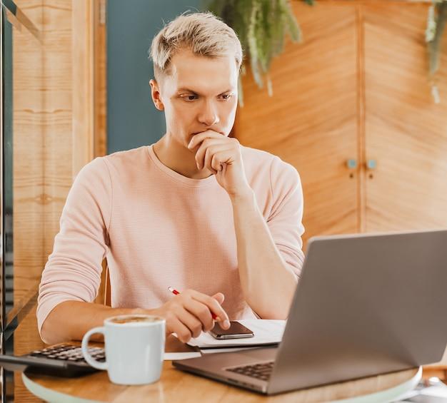 Szczęśliwy biznesmen siedzi w kawiarni z laptopem i smartfonem