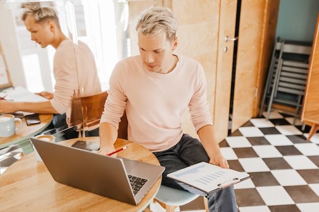 Szczęśliwy biznesmen siedział w kawiarni z laptopem i dokumentami. biznesmen siedzi w kawiarni, harmonogram pracy i sprawdzanie