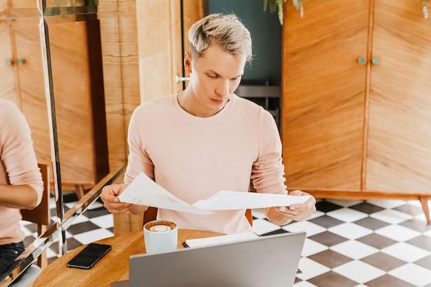 Szczęśliwy biznesmen siedział w kawiarni z laptopem i dokumentami. biznesmen siedzi w kawiarni, pracuje i sprawdza pocztę na komputerze