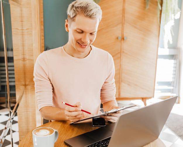 Szczęśliwy biznesmen siedział w kawiarni z laptopem i smartfonem.
