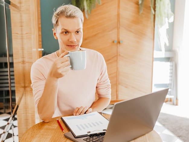 Szczęśliwy biznesmen siedział w kawiarni z laptopem i smartfonem