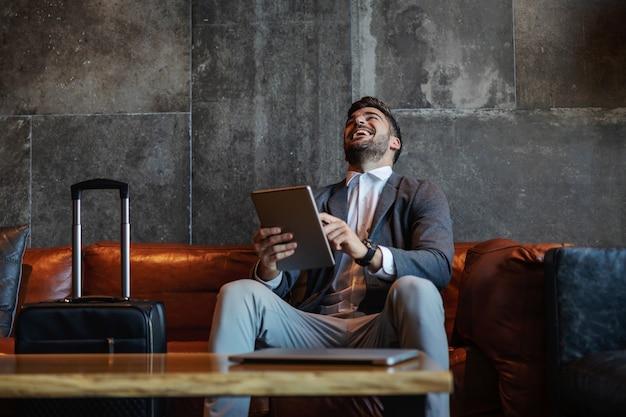 Szczęśliwy biznesmen, śmiejąc się i używając tabletu w podróży służbowej