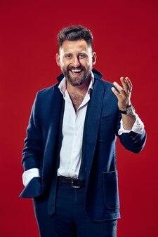Szczęśliwy biznesmen stojący i uśmiechnięty na białym tle na czerwonym studio.