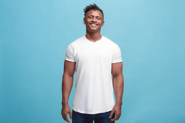 Szczęśliwy biznesmen stojący i uśmiechnięty na białym tle na niebieskim studio.