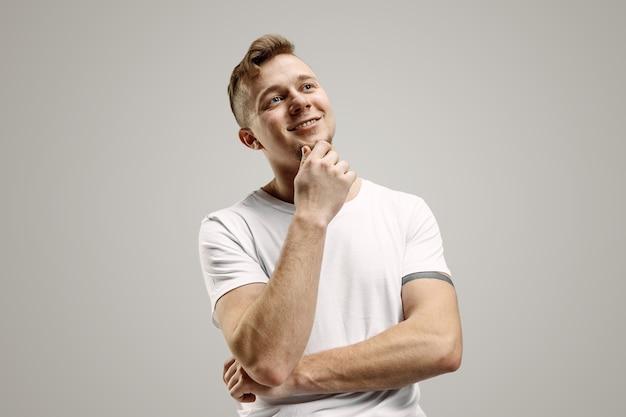 Szczęśliwy biznesmen stojący, uśmiechnięty na białym tle na szarym studio