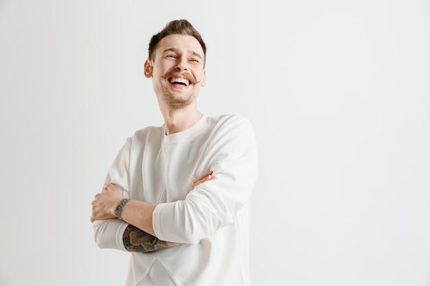 Szczęśliwy biznesmen stojący, uśmiechnięty na białym tle na szarym tle studio. piękny portret męski w połowie długości. młody człowiek zadowoli. ludzkie emocje, koncepcja wyrazu twarzy.