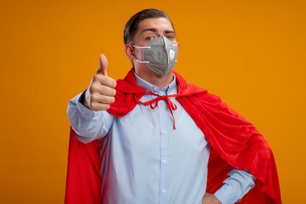 Szczęśliwy biznesmen super bohatera w ochronną maskę na twarz i czerwoną pelerynę patrząc na kamery pokazujące kciuki stojąc na pomarańczowym tle