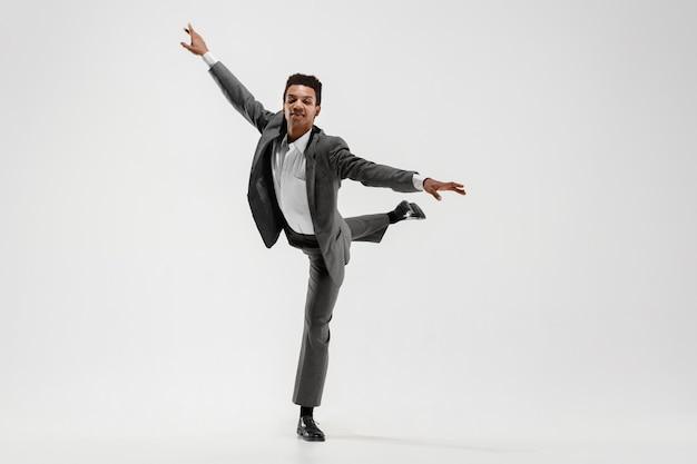 Szczęśliwy biznesmen taniec w ruchu na białym tle na tle białego studia. elastyczność i wdzięk w biznesie. koncepcja ludzkich emocji. biuro, sukces, zawodowość, szczęście, koncepcje ekspresji