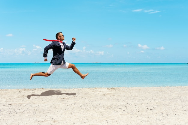Szczęśliwy biznesmen ucieka od pracy biurowej na plaży