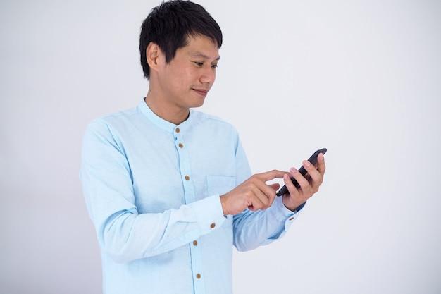 Szczęśliwy biznesmen używa smartphone.