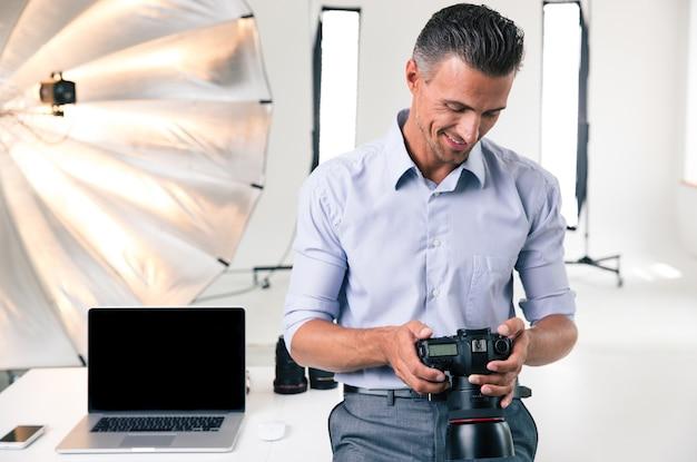 Szczęśliwy biznesmen używający aparatu w studio