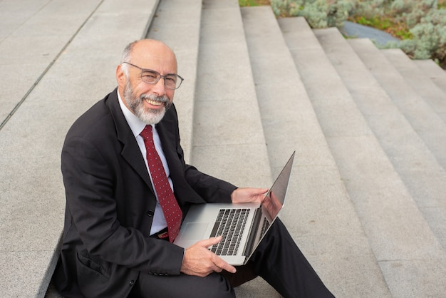 Szczęśliwy biznesmen w eyeglasses używać laptop na ulicie