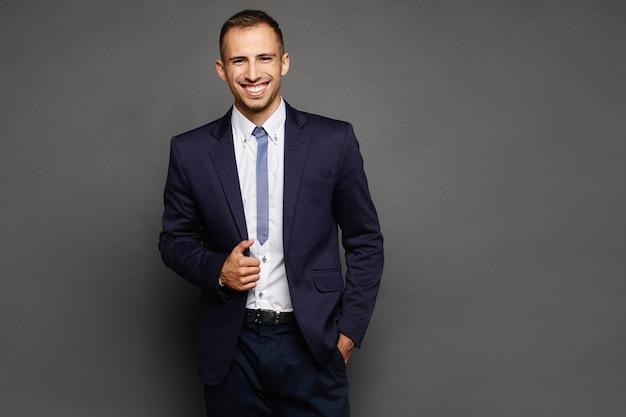 Szczęśliwy biznesmen w kostiumu odizolowywającym przy ciemnym tłem. przystojny młody mężczyzna w oficjalnym stroju pozowanie