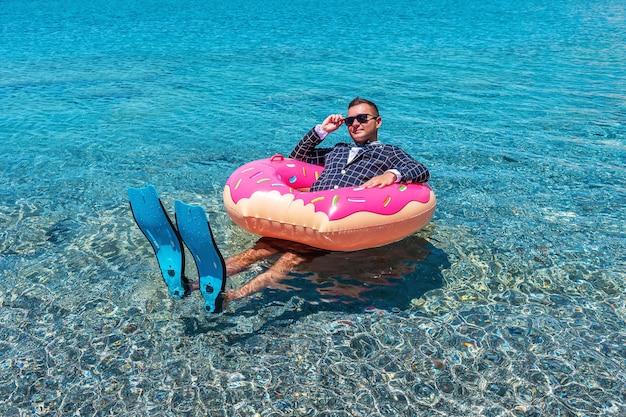 Szczęśliwy biznesmen w płetwach na nadmuchiwanym pączku na morzu.