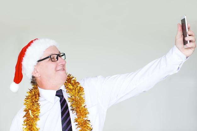 Szczęśliwy biznesmen w santa kapeluszu bierze selfie
