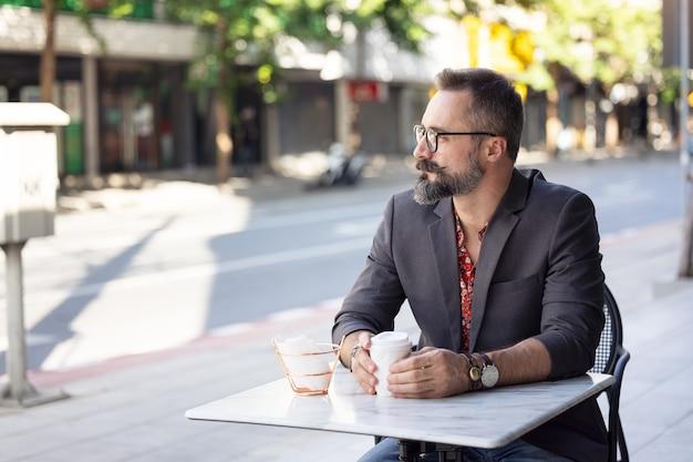 Szczęśliwy biznesmen w średnim wieku portret picia kawy na zewnątrz