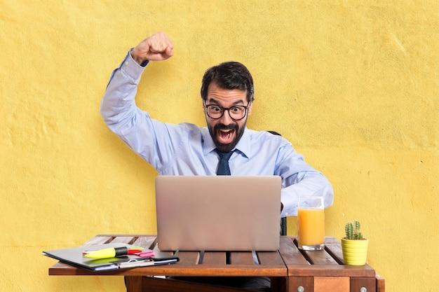 Szczęśliwy biznesmen w swoim biurze