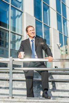 Szczęśliwy biznesmen z filiżanki kawy pozycją przed budynkiem