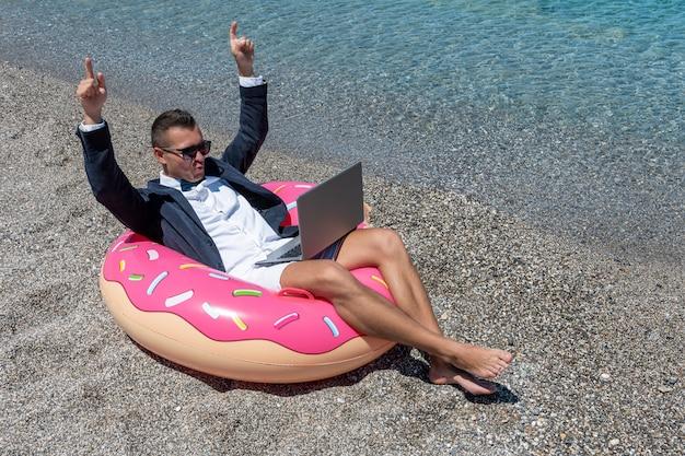 Szczęśliwy biznesmen z laptopem na nadmuchiwanym pączku na tropikalnej plaży