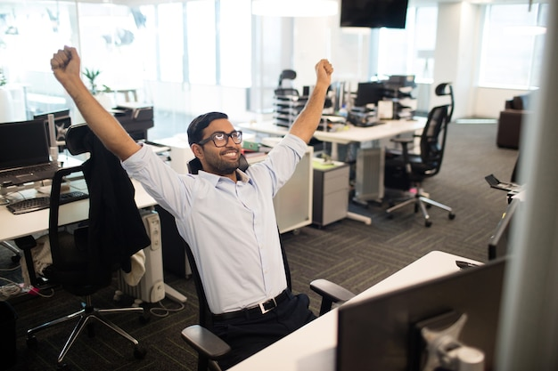 Szczęśliwy biznesmen z podniesionymi rękami w biurze