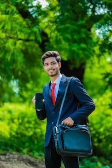 Szczęśliwy biznesmen z smartphone i walizką