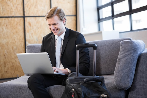 Szczęśliwy biznesmena obsiadanie na kanapie i używać laptopie w biurze