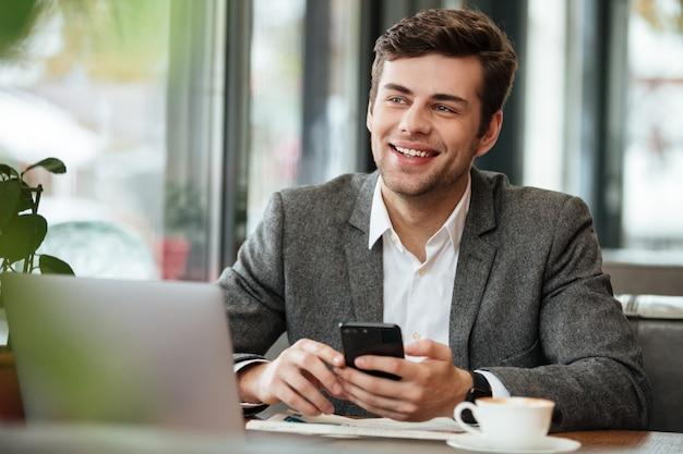 Szczęśliwy biznesmena obsiadanie stołem w kawiarni z laptopem i smartphone podczas gdy patrzejący daleko od