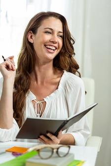 Szczęśliwy bizneswoman ono uśmiecha się podczas gdy trzymający notepad przy biurkiem
